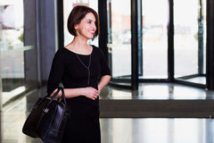 Usinesswoman in black dress walking with briefcase in contempora. Office worker, beautiful young businesswoman in black dress walking with briefcase in royalty free stock photo
