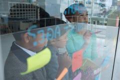 Usinesswoman explaining to colleagues seen through window Stock Photo