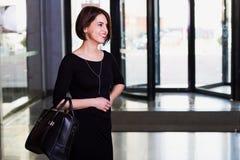Usinesswoman im schwarzen Kleid, das mit Aktenkoffer im contempora geht Lizenzfreies Stockfoto