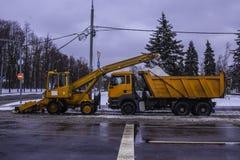 Usinez les pelles neigent de la rue et de la neige de chargement dans un camion Images stock