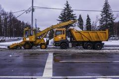 Usinez les pelles neigent de la rue et de la neige de chargement dans un camion Photos stock