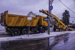 Usinez les pelles neigent de la rue et de la neige de chargement dans un camion Image libre de droits