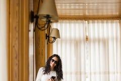 Usinf Porträt der jungen Frau zuhause intelligentes Telefon Stockfotografie