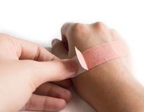 Using an Adhesive plaster. On whited background Stock Images