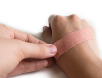 Using an Adhesive plaster. On whited background Royalty Free Stock Photo