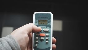 Using air conditioner remote control closeup. Setting an air conditioner at a lower temperature.  stock footage