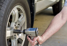 Using air wrench to remove car tire Stock Photo