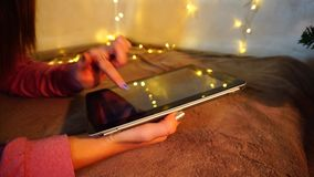 Using amazing tablet in cozy atmosphere. Coloured nails touching screen. Yellow twinkling lights as Christmas decoration. Concept of working with modern device stock video footage