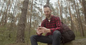 Using App in the Forest. Traveller bearded man using smartphone app while relaxing in the forest stock footage