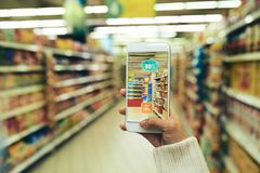Using Augmented Reality App at Supermarket. Unrecognizable young woman using augmented reality app while doing shopping in supermarket, focus on foreground Royalty Free Stock Image