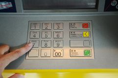 Using bank ATM. Men hand dialing pin on bank ATM keyboard royalty free stock image