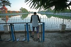 A women works out on the free exercise equipment on the walkway around the Mandalay fort complex in Myanmar royalty free stock image