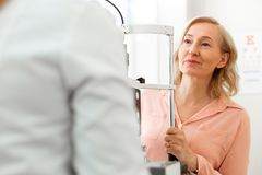 Curious blonde lady attentively listening to conclusions of her doctor. Using big apparatus. Curious blonde lady attentively listening to conclusions of her stock image