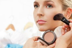 Using blush brush to apply blush on cheeks. Professional makeup artist working stock image