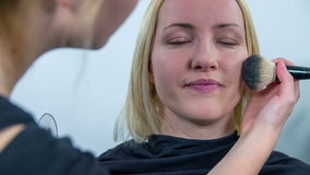 Using the brash to puff the face of a woman stock footage