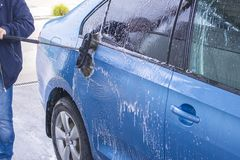 Using a brush to wash a car on a car washing facility on sunny summer day.Manual car wash with pressurized water in car wash royalty free stock photo
