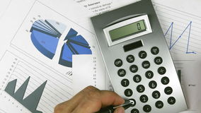 Using calculator. On and off the calculator lying in the diagram, charts stock footage