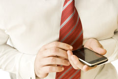 Using a cell phone. Close up of businessman hands using a cell phone Stock Images