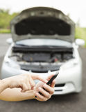 Using cell phone to dial service number , a broken car Stock Image