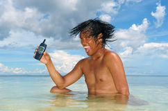 Using a cell-phone in a tropical sea. Stock Image