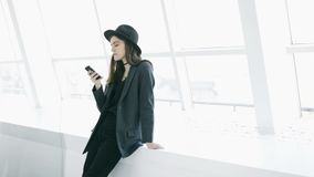 Using cell phone young beautiful woman in light white interior. Video footage. Fashion casual style stock footage