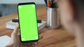 Using cellphone with green screen close up. Businesswoman using cellphone with green screen in workplace. Concept of copy space advertising for application stock video footage
