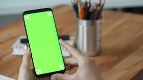 Using cellphone with green screen close up. Person hold cellphone with green screen display in hand in workplace. Close up concept of copy space advertising for stock video