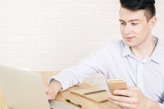 Using cellphone and laptop Stock Image