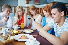 Using cellphones. Modern teens with their cellphones sitting in cafe Royalty Free Stock Image