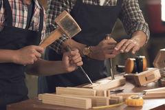 Using chisel. Carpenter teaching pupil how to use chisel Royalty Free Stock Photography