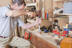 Using chisel on workbench. Man using chisel at workbench surrounded by tools and equipment Stock Photography