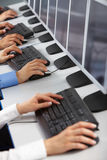 Using computers. Image of row of human hands typing in computer classroom Stock Photography
