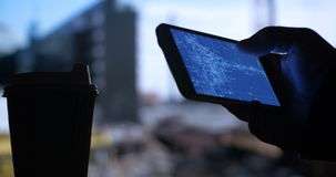 Using construction blueprints on Smart Phone. Close up of man's hand using mobile cell smart phone to check construction blueprints while drinking coffee tea stock footage