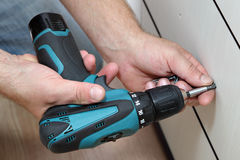 Using cordless screwdriver for screwing screws when assembling f Royalty Free Stock Images