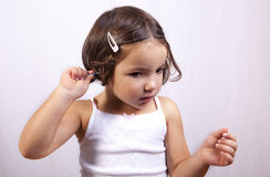 Using cotton bud to clean her ear by himself. Young latin girl use white cotton bud to clean her ear by himself stock photos