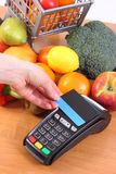 Payment terminal with contactless credit card and fresh fruits and vegetables, cashless paying for shopping. Using credit card reader, payment terminal with Stock Photography