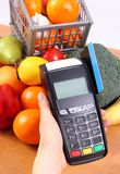 Payment terminal with credit card and fresh fruits and vegetables, cashless paying for shopping. Using credit card reader, payment terminal with credit card Stock Photography