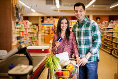 Using a credit card at the store. Cute happy couple paying for their food at the checkout counter with a credit card Stock Photo