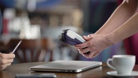 Using Credit Card Terminal in cafe. Close-up, male hands with a credit card. Payment without contact method. Hands of the waiter in the frame stock video