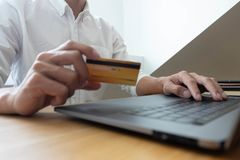 Using a credit card to pay online, use a smartphone for online shopping, a male hand holds a credit card royalty free stock photos