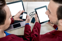 Using different digital gadgets. With empty white screens on the table Stock Photography