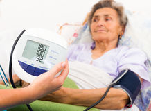 Using Digital Blood Pressure Gauge. Home care nurse using digital blood pressure measure stock images