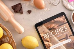 Using digital cookbook app in tablet in pastry stock image