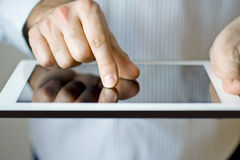 Using a digital tablet. Hands of a man using a digital touch screen tablet stock image
