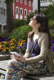 Using Digital Tablet and sunbathing in the park Royalty Free Stock Photography