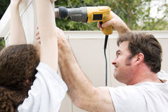 Using the Drill. Father and daughter working on home improvement project.  He's using the drill Royalty Free Stock Photo
