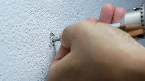 Using electric screwdriver to tighten the screw into plastic plug. Man hand using electric screwdriver to tighten the screw into plastic plug , wall anchors in stock footage