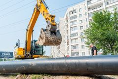 Using of excavator as crane for raising of tube Stock Photos
