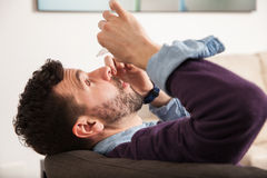 Using eye drops for redness. Profile view of a young man laying back on a couch and pouring some eye drops at home Royalty Free Stock Image