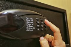 Using forefinger / index finger pushing number button on black safe to unlock safe or set password for safe. Using forefinger / index finger pushing number Royalty Free Stock Photos